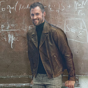 Kevin Love in a leather jacket infront of a chalkboard